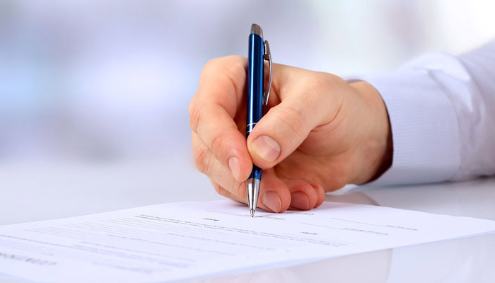 man holding pen and writing on paper